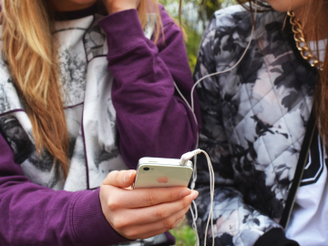 Kids listening to music on a cell phone.