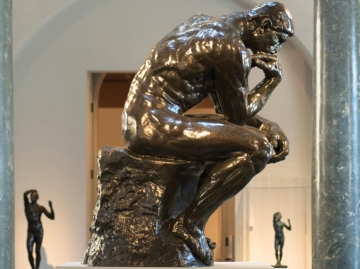 "The Thinker, by Auguste Rodin, is on view at Cantor Arts Center. An image of the statue also appears on brochures celebrating the ""Thinking Big About Learning"" symposium on Oct. 18. (Tamer Shabani)"