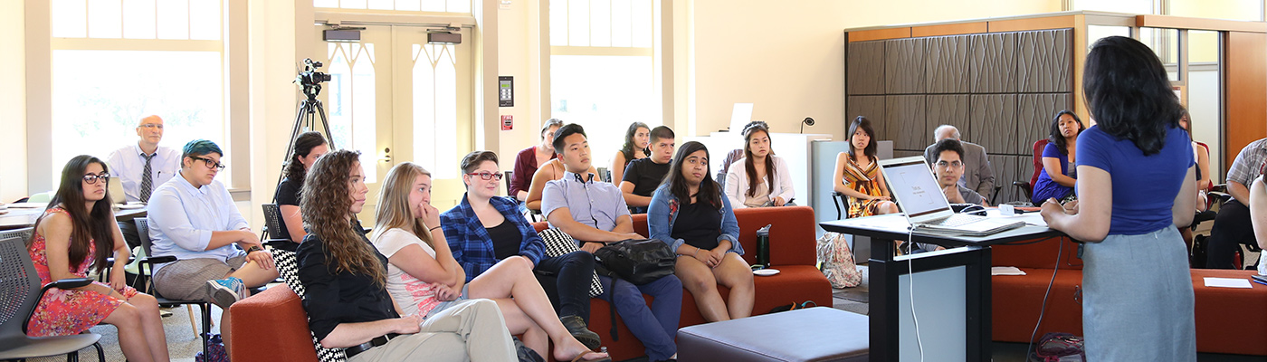 Photo of undergraduate students paying attention to fellow student presenting